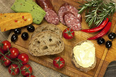Cheese, salami and bread  on a board Royalty Free Stock Photos
