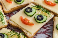 Sandwich with face from cucumbers, tomato, olives and dill