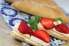 Cheese sandwich with strawberries. Brie cheese with strawberries on a bun with sesame seeds. soft focus stock images
