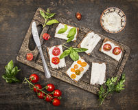 Cheese sandwiches with tomatoes on a branch and herbs on a cutting board with a knife on wooden rustic background top view Royalty Free Stock Photography