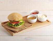 Cheese sauce, ketchup, mustard and hamburger Royalty Free Stock Photo