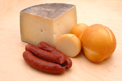 Cheese and sausage. Different cheese and salami rustically on a wooden underground stock photography