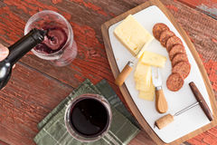 Cheese and Sausage on Board with Glasses of Wine Stock Image