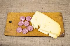 Cheese with sausage on a cutting wooden board stock photo