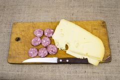 Cheese with sausage and a knife on a cutting wooden board stock photography