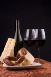 Cheese, sausages and wine. Cheese cubes, sausages and red wine served on a table stock photos