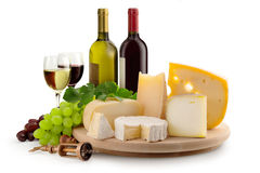Cheese selection. Cheeseboard, grapes, wineglasses and wine bottles Royalty Free Stock Photography