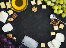Cheese selection with fresh grapes, walnuts and honey on a dark Royalty Free Stock Photos