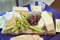 Cheese selection with grapes and celery Royalty Free Stock Photo