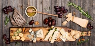 Free Cheese Selection On Wooden Rustic Board. Cheese Platter With Different Cheeses, Grapes, Nuts, Honey And Dates On Weathered Wood B Stock Images - 117083204