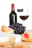 A cheese selection with wine. A cheese selection with a bottle and half a glass of red wine in the background Royalty Free Stock Photography