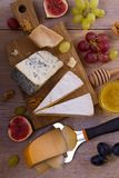 Cheese selection on wooden rustic background. Cheese platter with different cheeses, served with grapes, figs, nuts and honey Royalty Free Stock Photography