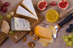 Cheese selection on wooden rustic background. Cheese platter with different cheeses, served with grapes, figs, nuts and honey Stock Photography
