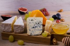 Cheese selection on wooden rustic background. Cheese platter with different cheeses, served with grapes, figs, nuts and honey Stock Image