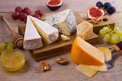 Cheese selection on wooden rustic background. Cheese platter with different cheeses, served with grapes, figs, nuts and honey Stock Photo