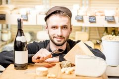 Cheese seller portrait. Close-up portrait of a young sommelier or cheese seller with cheese assortment and wine bottle in front of the store showcase royalty free stock images