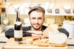 Cheese seller portrait. Close-up portrait of a young sommelier or cheese seller with cheese assortment and wine bottle in front of the store showcase stock image