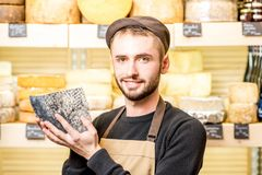 Cheese seller at the shop. Portrait of a handsome cheese seller in uniform holding a peace of seasoned cheese in front of the store showcase full of different stock photo