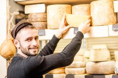 Cheese seller at the shop. Cheese seller putting goods on the shelves at the cheese store stock photography