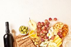 Cheese set on a plate laid out on a beige background. Different types of cheeses: Camembert, Parmesan, blue cheese, olives, honey,. Grapes royalty free stock photography