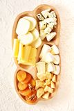 Cheese set on a plate laid out on a beige background. Different types of cheeses: Camembert, Parmesan, blue cheese, olives, honey,. Grapes stock images