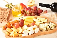 Cheese set on a plate laid out on a beige background. Different types of cheeses: Camembert, Parmesan, blue cheese, olives, honey,. Grapes stock photography