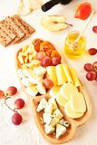 Cheese set on a plate laid out on a beige background. Different types of cheeses: Camembert, Parmesan, blue cheese, olives, honey,. Grapes stock image
