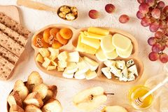 Cheese set on a plate laid out on a beige background. Different types of cheeses: Camembert, Parmesan, blue cheese, olives, honey,. Grapes royalty free stock photos