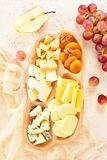 Cheese set on a plate laid out on a beige background. Different types of cheeses: Camembert, Parmesan, blue cheese, olives, honey,. Grapes stock photo
