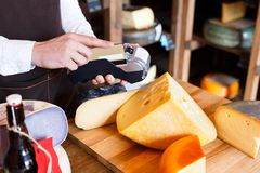 Cheese shop assistant swipe credit card. At counter, paying for order in grocery Royalty Free Stock Photography