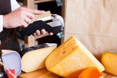Cheese shop assistant swipe credit card. At counter, paying for order in grocery Stock Photos