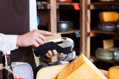 Cheese shop assistant swipe credit card. At counter, paying for order in grocery Stock Images