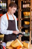 Cheese shop assistant swipe credit card. Paying for order of in grocery. Man seller. Vertical Royalty Free Stock Photo