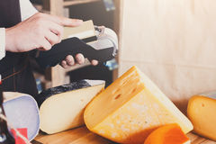 Cheese shop assistant swipe credit card. At counter, paying for order in grocery Stock Photo