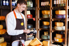 Cheese shop assistant swipe credit card. Paying for order of in grocery Royalty Free Stock Photos