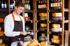 Cheese shop assistant swipe credit card. Paying for order of in grocery Royalty Free Stock Photo
