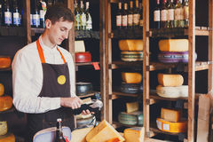 Cheese shop assistant swipe credit card. Paying for order of in grocery Stock Photos