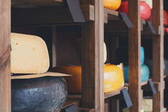 Cheese shop shelves closeup, large assortment. Cheese shop shelves closeup. Assortment of cheese wheels in store. Focus on parmesan piece royalty free stock photo