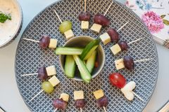 Cheese skewers and cucumber on plate stock photo