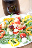 Cheese skewers for starter, with mozzarella, tomatoes, sweet pepper and olives, on fresh rocket salad, red vine Royalty Free Stock Photography