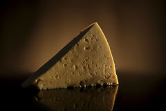Cheese slice. Yellow cheese slice - isolated on dark background Royalty Free Stock Images