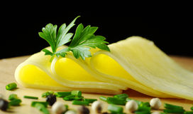 Cheese Slices. Garnished with a parsley leaf and some shallot and pepper corns in the foreground on wooden board with black background (Selective Focus, Focus stock images