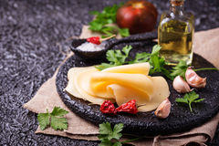 Cheese slices on cast iron board. Selective focus royalty free stock images