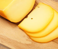 Cheese slices on cutting board Royalty Free Stock Photo