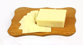 Cheese Slices Cutting Board. A block of sharp cheddar cheese and slices Royalty Free Stock Photos