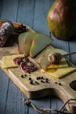 Cheese with slices of pear. Salami and honey on wooden cutting board Royalty Free Stock Image