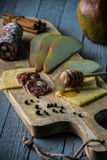Cheese with slices of pear. Salami and honey on wooden cutting board Stock Photography