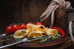 Cheese slices on a wooden board. Cheese rolls on a wooden board with tomatoes, chili and herbs. Wooden wine box. Copy space stock images
