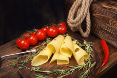 Cheese slices on a wooden board. Cheese rolls on a wooden board with tomatoes, chili and herbs. Wooden wine box. Copy space royalty free stock photo