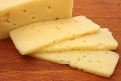 Cheese slices. On a wooden cutting board Royalty Free Stock Photography